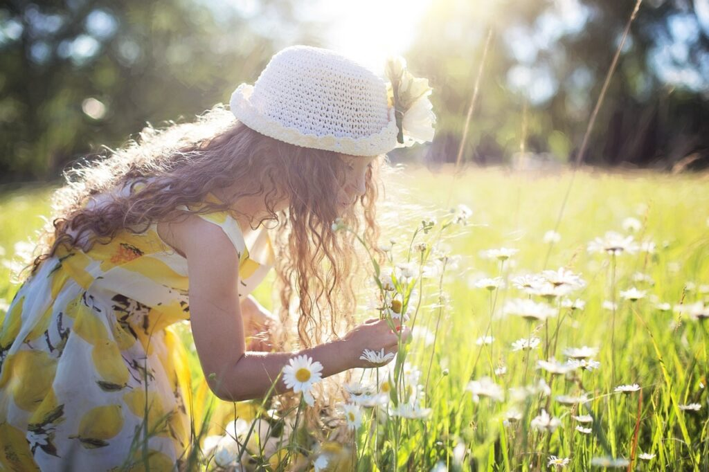 girl in sundress picking flowers in a meadow in the spring lice free