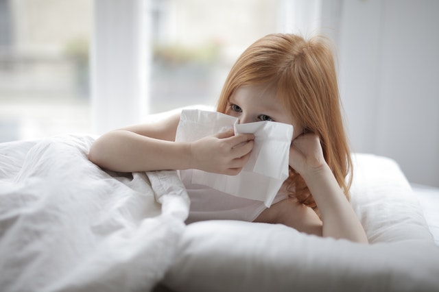 child blowing their nose into a tissue while laying in bed