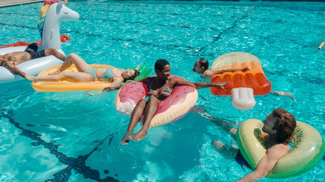 family swimming on floaties in swimming pool
