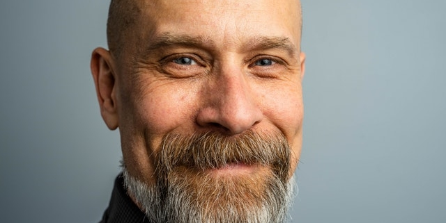 bald man with beard in front of gray blue screen